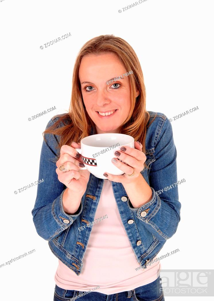 Stock Photo: A young woman in a jeans jacket standing and holding a big mug of hot sup on a cold winter day, isolated for white background.