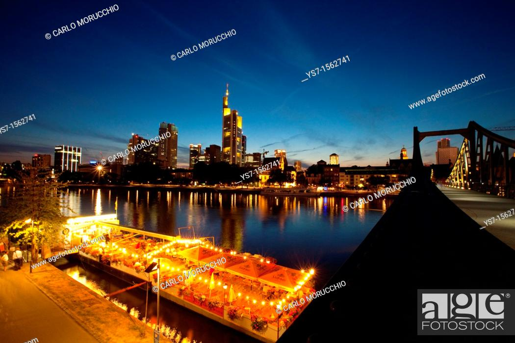 Imagen: The Frankfurt am Main skyline and boat restaurants moored on the Main river, seen from Alte brücke bridge at sunset, Germany, Europe.