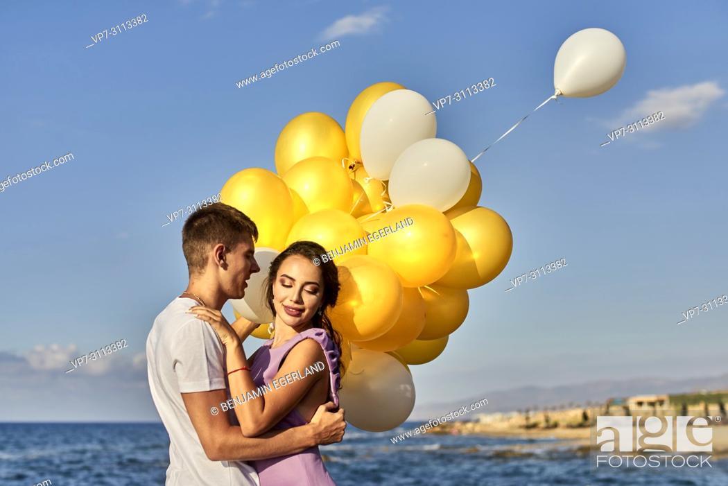 Stock Photo: couple embracing, balloons, seaside.