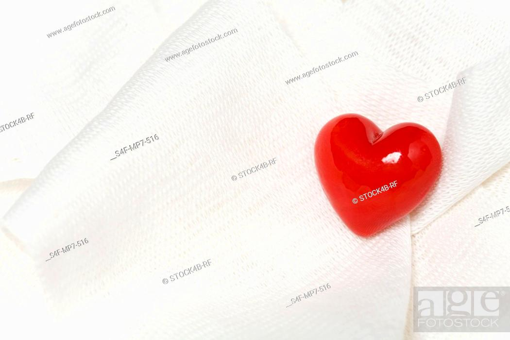 Stock Photo: Red heart on white cloth.