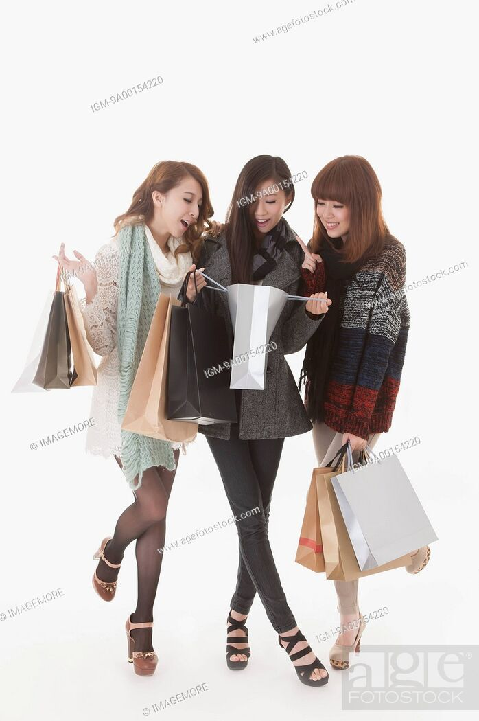 Imagen: Girlfriends shopping together and looking into shopping bag.