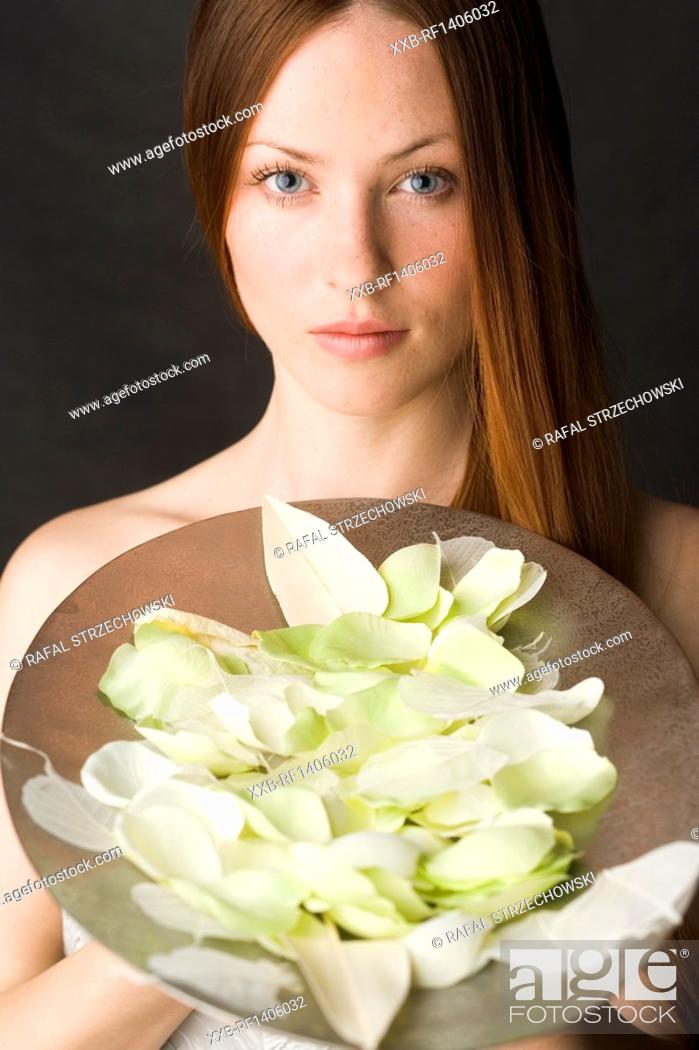 Stock Photo: young woman with petals on trace.