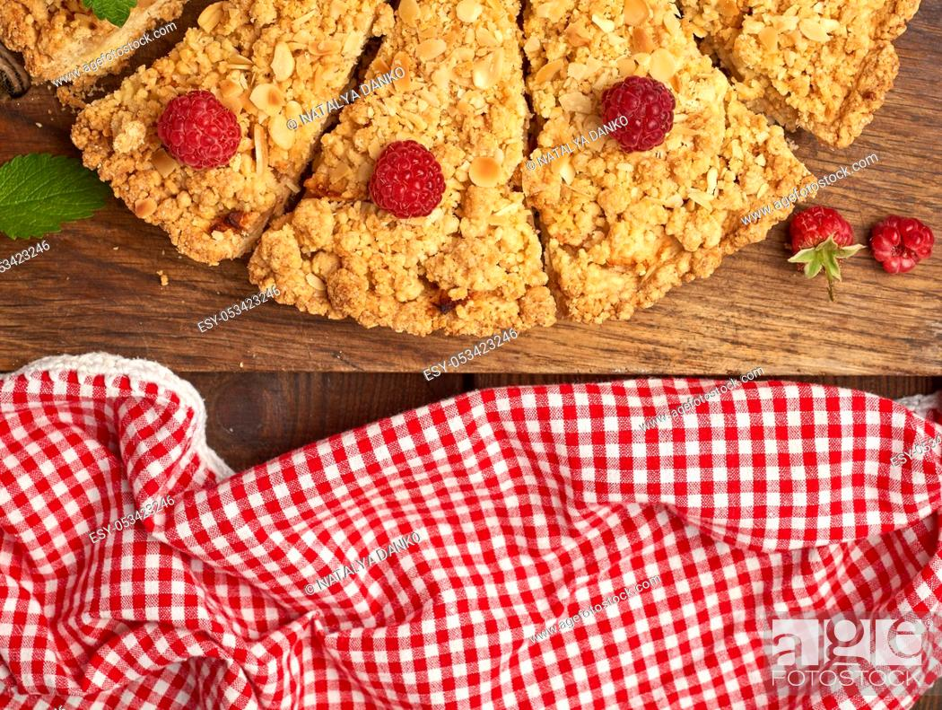 Photo de stock: sliced triangular pieces of crumble pie with apples on a brown wooden board, top view.