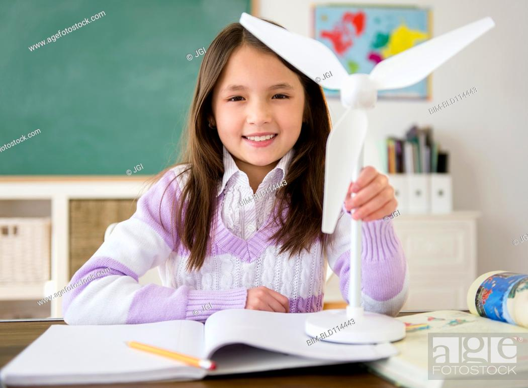 Stock Photo: Mixed race girl holding model wind turbine in class.