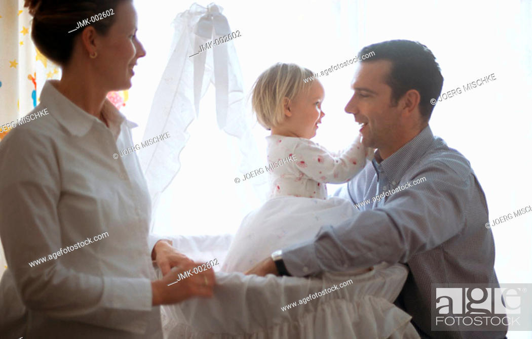 Stock Photo: A young couple, young man and young pregnant woman, 25-30 30-35 35-40 years old, in the nursery in front of the cradle with their little daughter, 1-5 years old.
