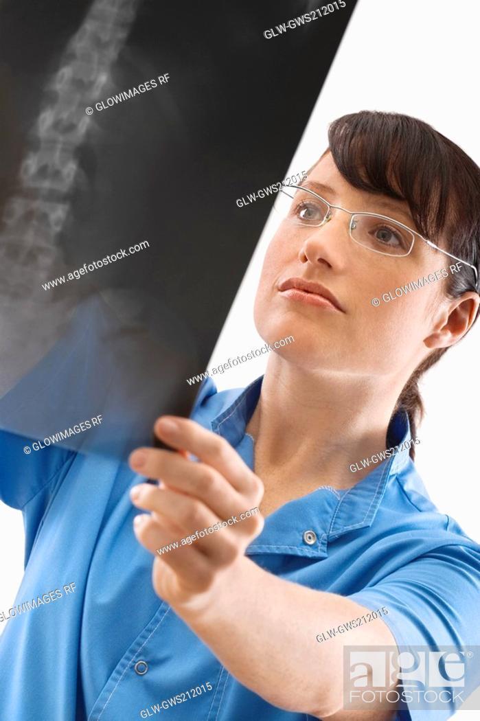 Stock Photo: Female surgeon examining an X-Ray.
