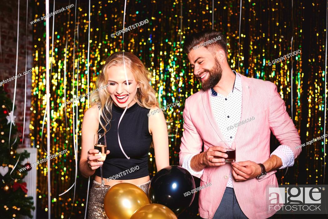 Stock Photo: Man and woman at party, holding drinks, laughing.