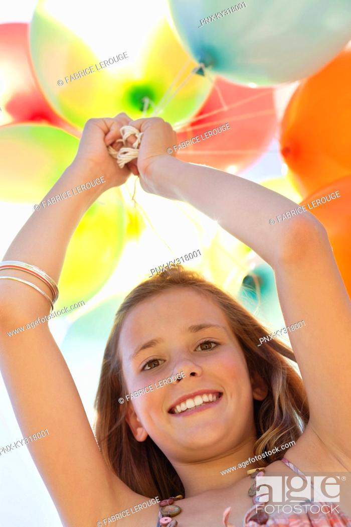 Stock Photo: Portrait of a girl playing with balloons and smiling.