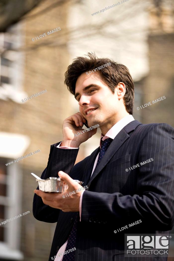Stock Photo: A businessman talking on his mobile phone, eating take-away food.