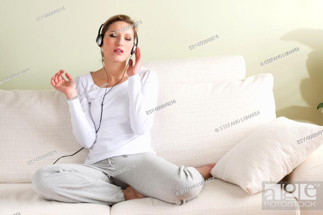 Stock Photo: Young woman listening to music on sofa.