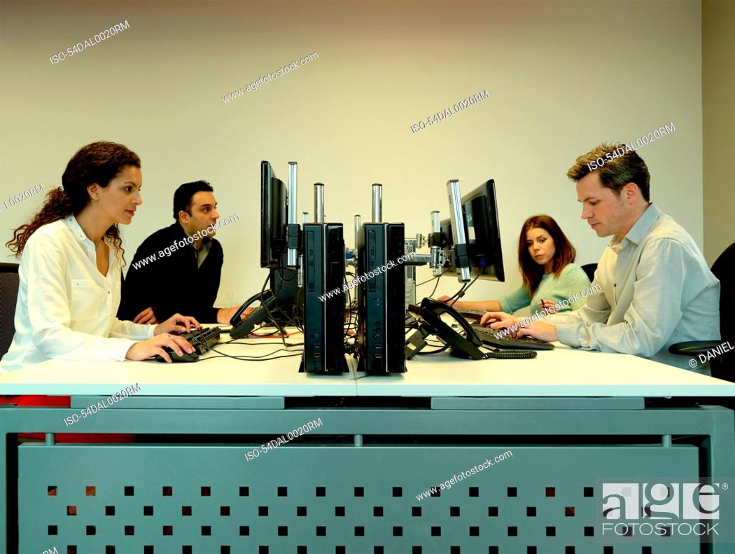 Stock Photo: Business people using computers at desk.