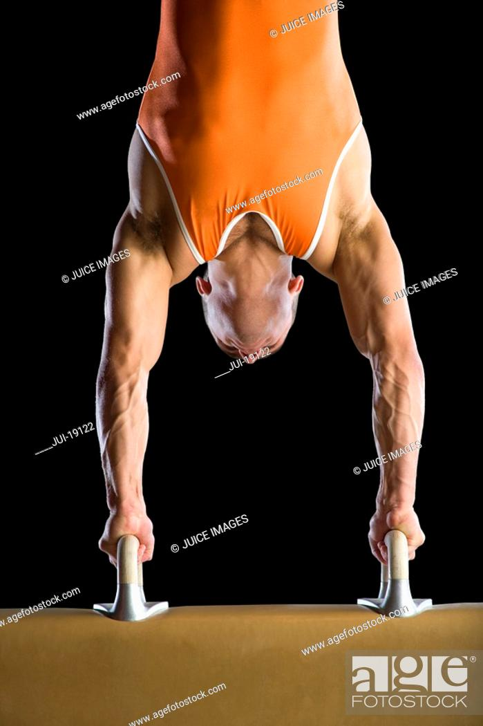 Stock Photo: Male gymnast performing handstand on pommel horse, close-up.
