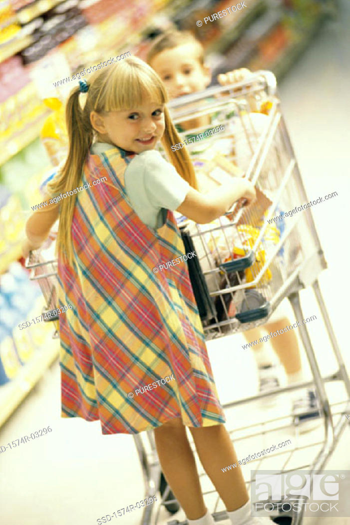 Stock Photo: Girl and a boy playing with a shopping cart in a supermarket.