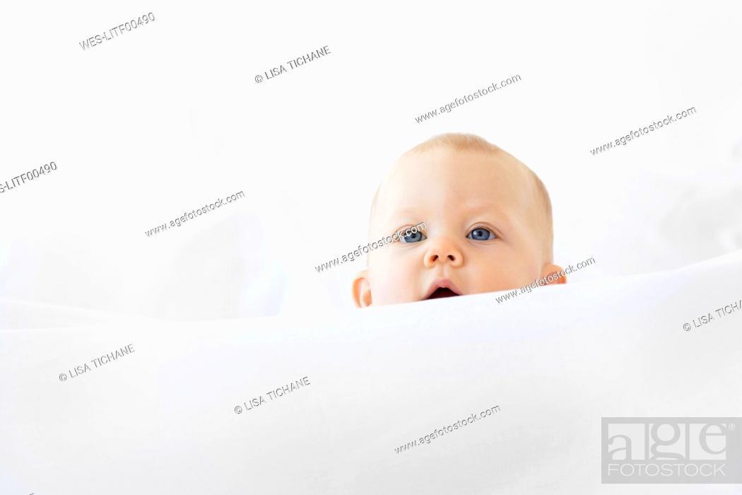 Stock Photo: Baby girl peeking over white bed sheet.