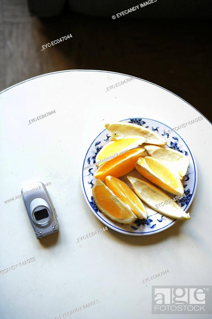 Stock Photo: Slices of orange and mobile phone on table.