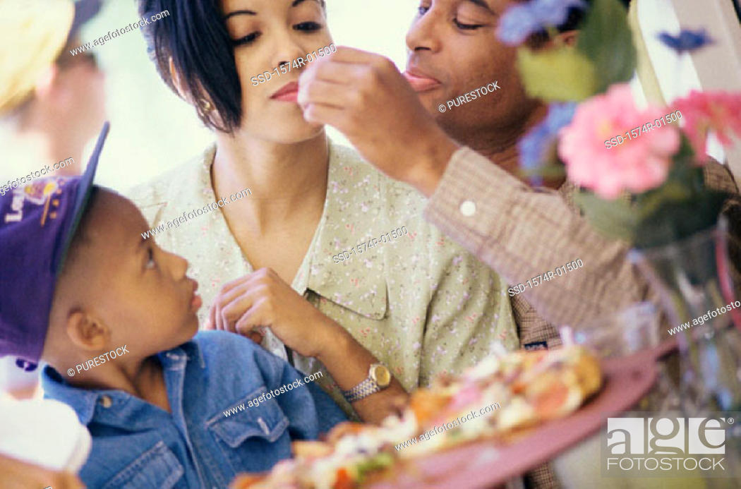 Stock Photo: Close of a young couple eating pizza with their son.