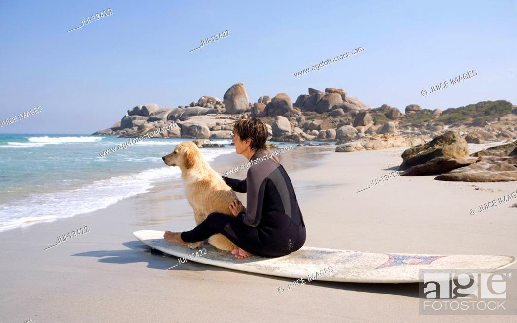 Stock Photo: Female surfer with dog on surfboard on beach, side view.