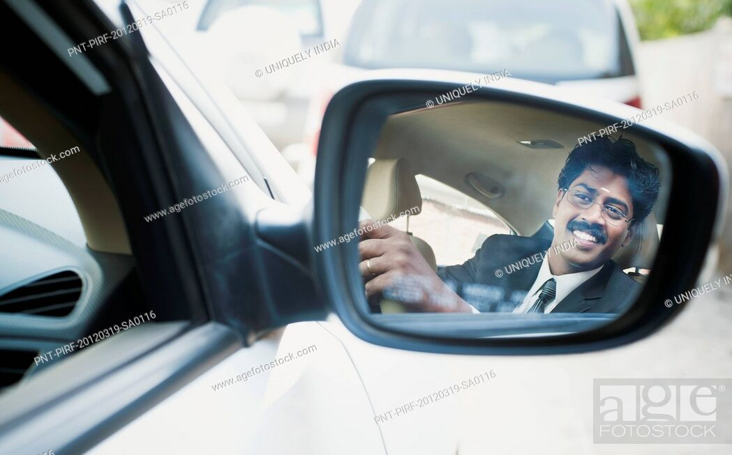 Stock Photo: Reflection of a South Indian businessman in the side view mirror of a car.