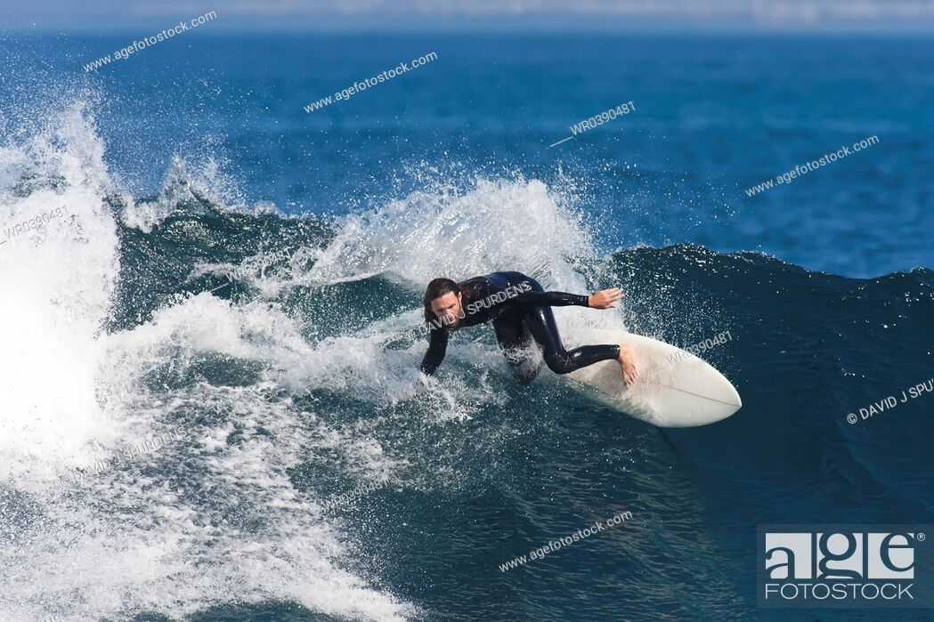 Stock Photo: Surfer rides fast along breaking wave.