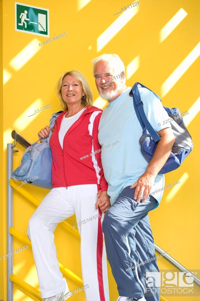 Stock Photo: Senior couple walking up stairs with gym bags, smiling, low angle view.