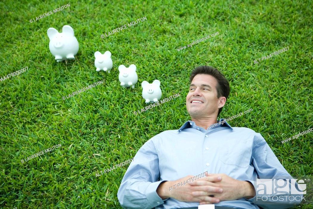 Stock Photo: Man lying on grass, next to piggy banks, smiling.