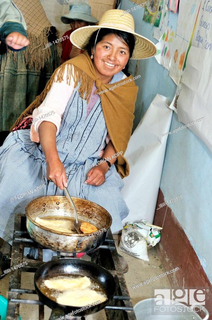 Photo de stock: Woman in traditional dress of the Quechua preparing fried dumplings, Bolivian Altiplano highlands, Departamento Oruro, Bolivia, South America.