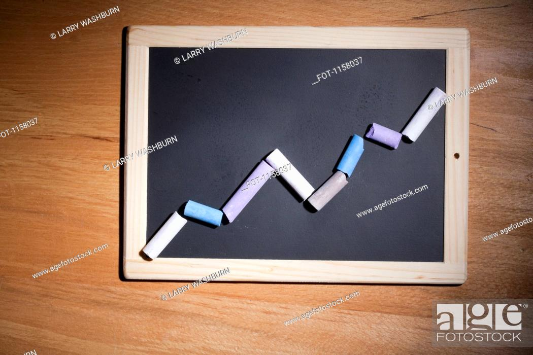 Stock Photo: A line graph showing growth made with pieces of chalk and a chalkboard.
