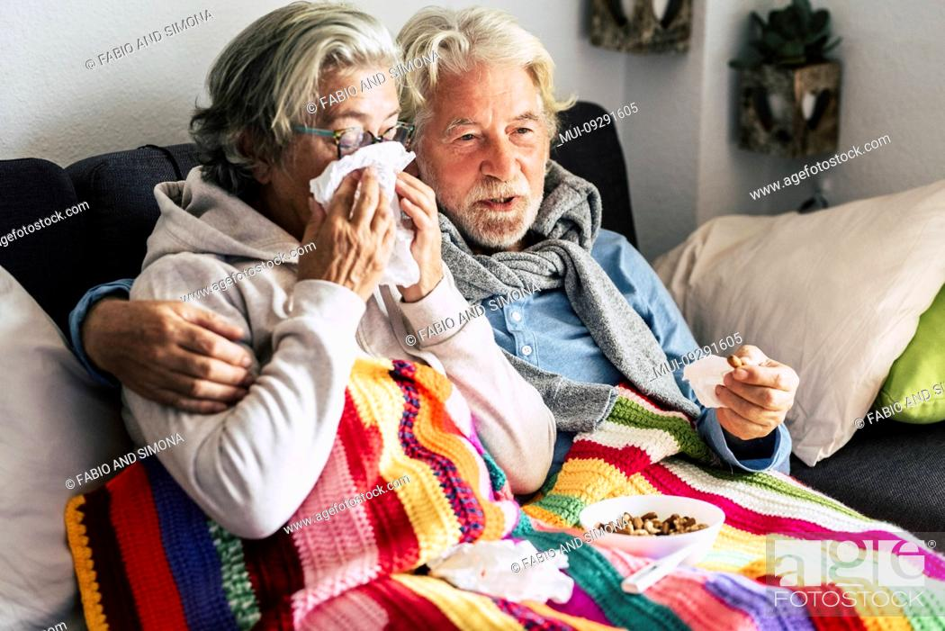 Stock Photo: Couple of old aged senior people at home with seasonal winter cold illness disease sit down on the sof together forever - health problems for retired man and.