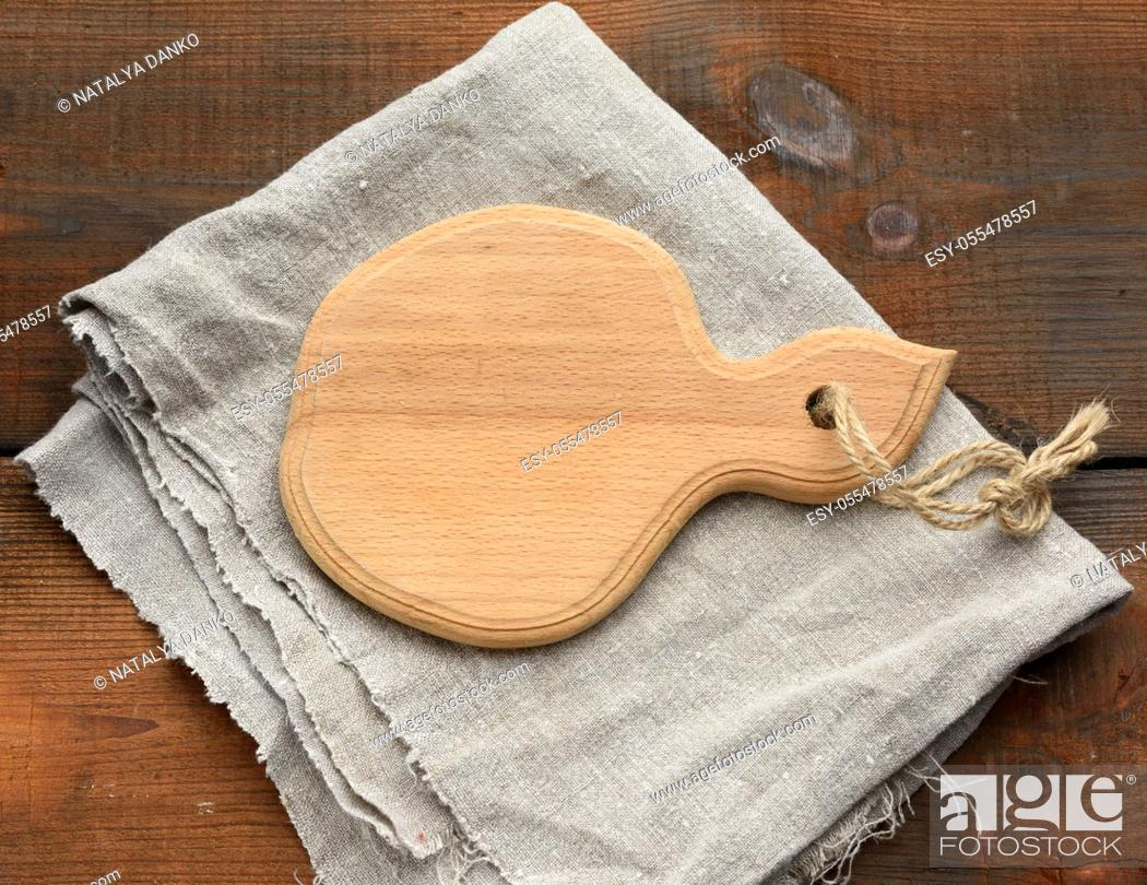 Stock Photo: brown wooden kitchen cutting board and gray linen napkin on the table, top view.