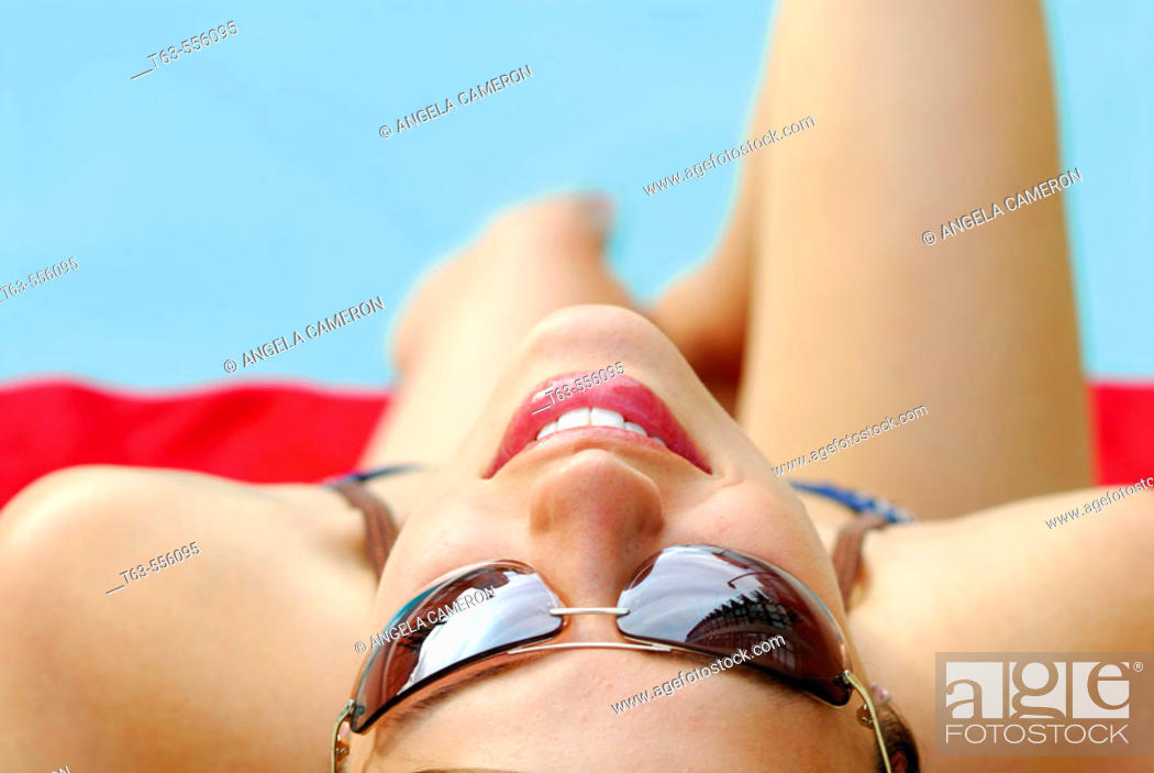 Stock Photo: 20 yr old woman laying by pool with sunglasses on.