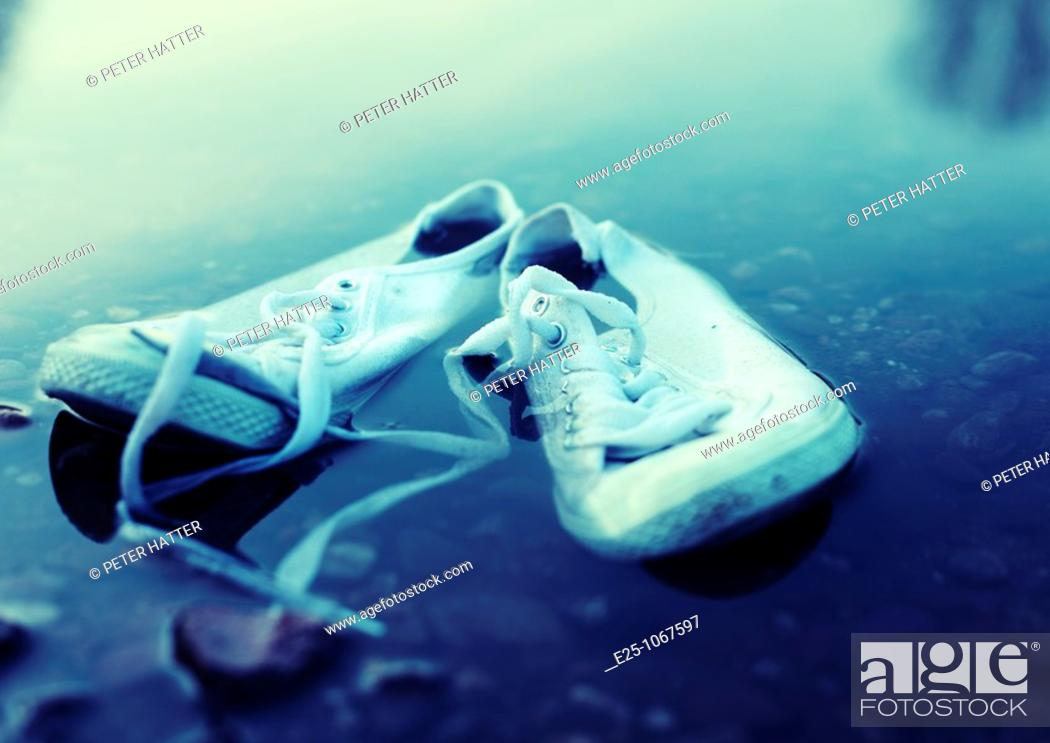 Stock Photo: A pair of plimsolls lay in the water close to the riverbank.