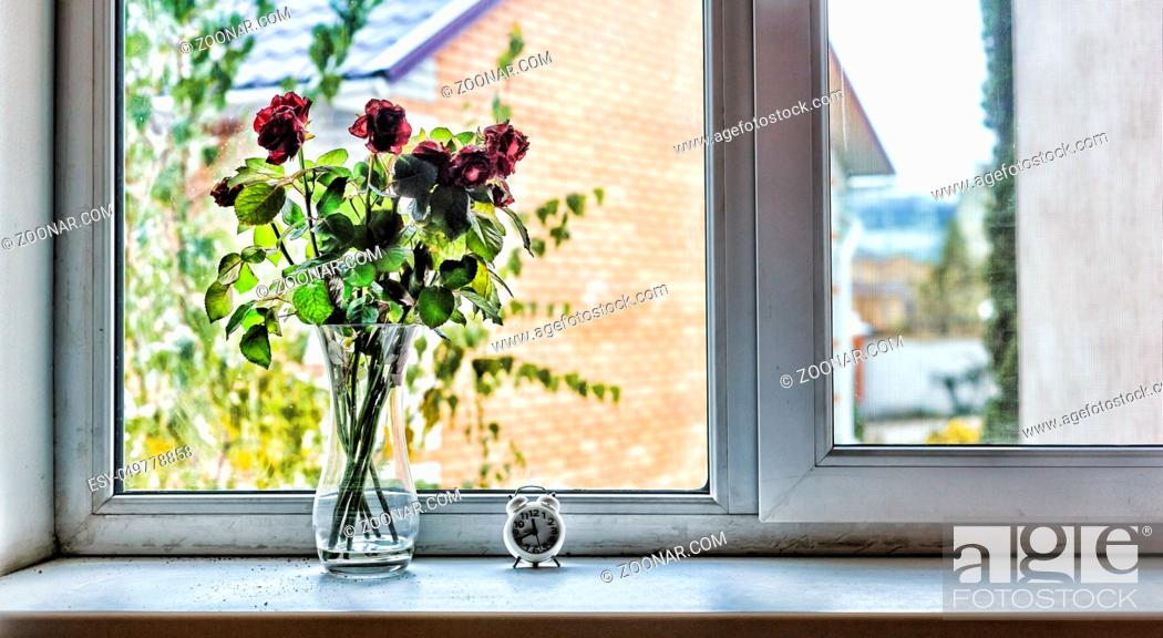 Stock Photo: A bouquet of beautiful roses on the windowsill in the house. Concept: Love, St. Valentine's Day, Birthday, anniversary of the wedding.