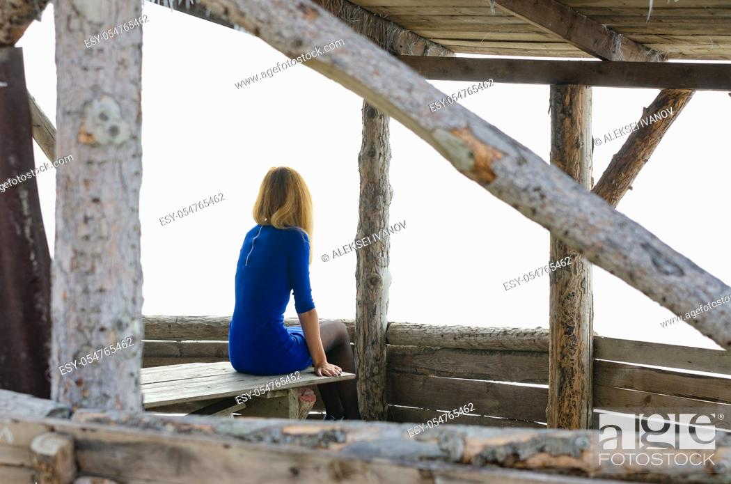 Stock Photo: A girl sits on a table in a gazebo from a log house.