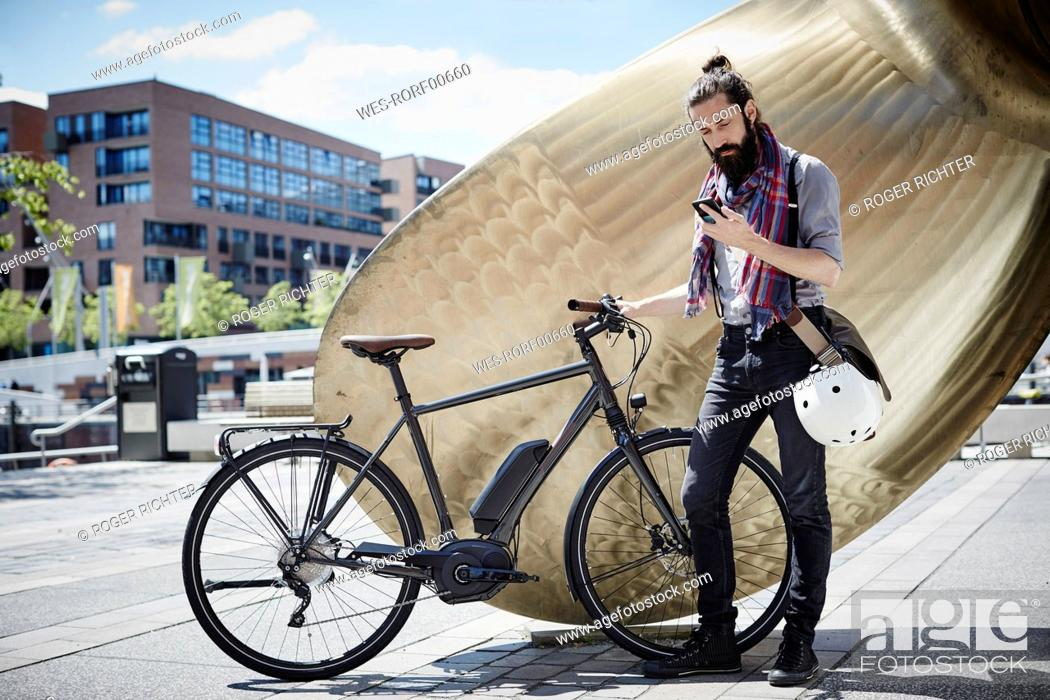 Stock Photo: Man with electric bicycle looking at his cell phone.