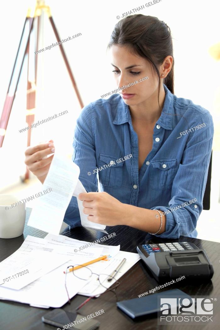 Stock Photo: Woman at desk looking at receipts.