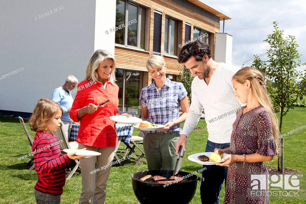 Stock Photo: Germany, Bavaria, Nuremberg, Family standing around barbecue in garden.