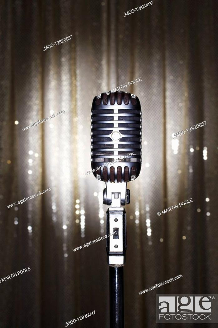 Stock Photo: Old fashioned microphone in front of stage curtain.