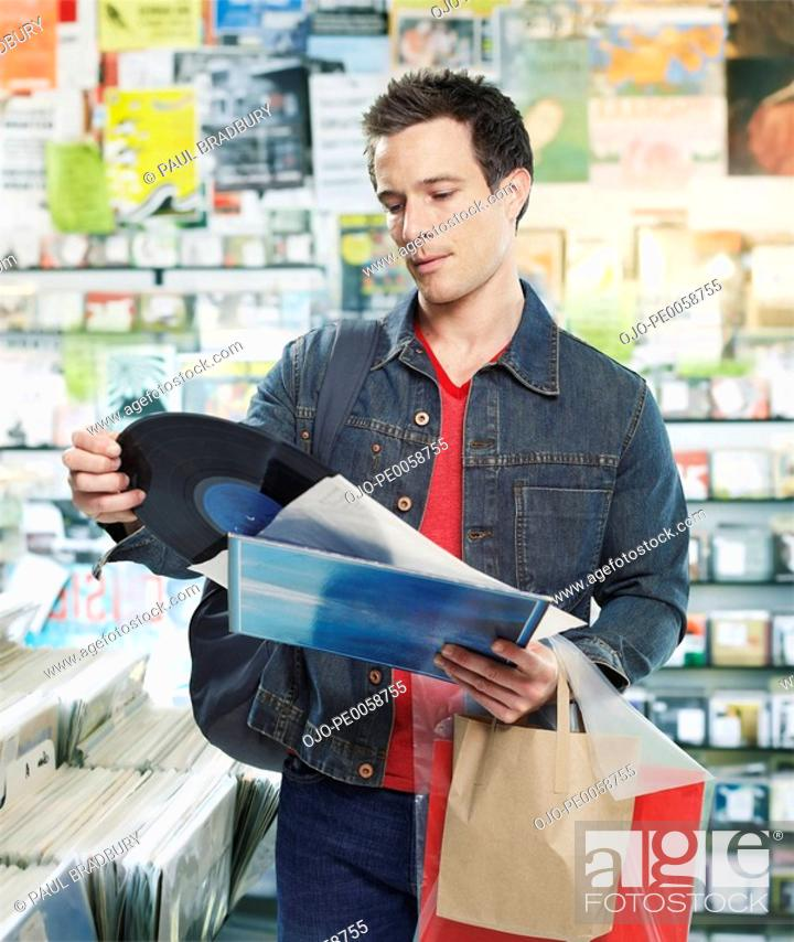 Stock Photo: Man looking at record in store.