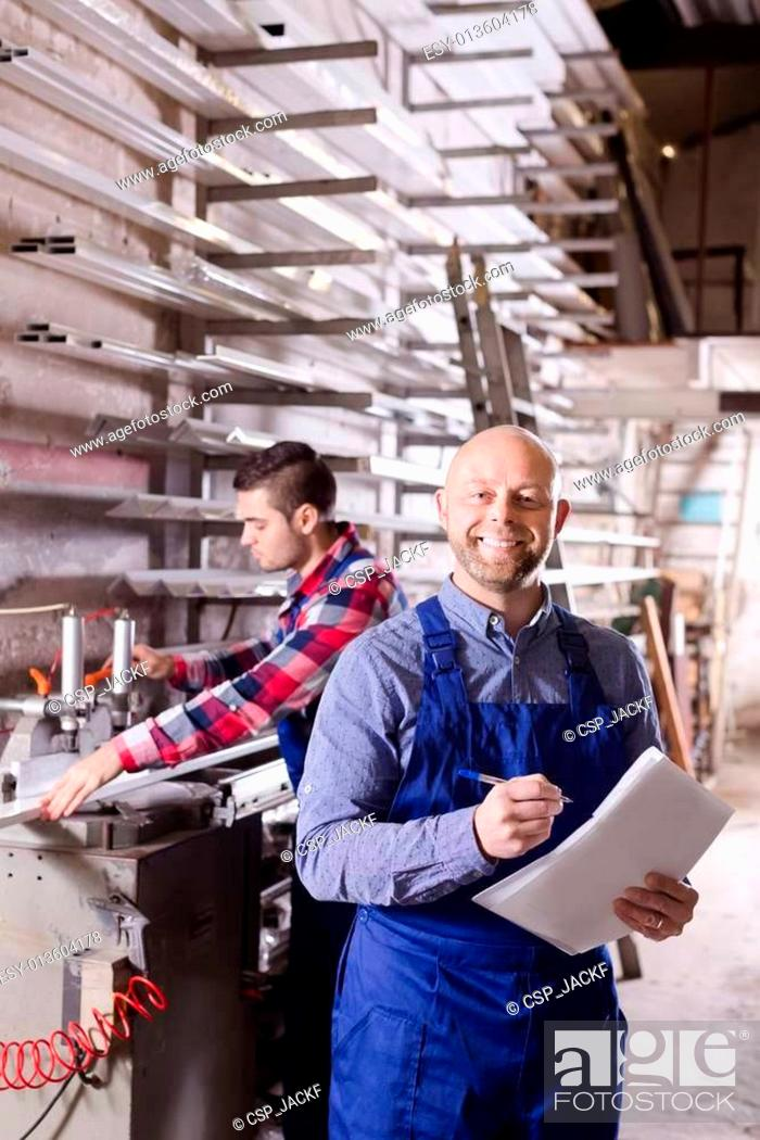 Stock Photo: Two smiling workmen at factory.