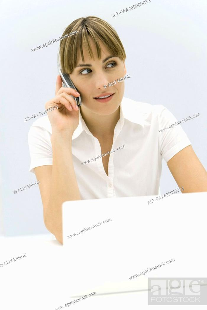 Stock Photo: Woman sitting in front of laptop computer, using cell phone, looking away.