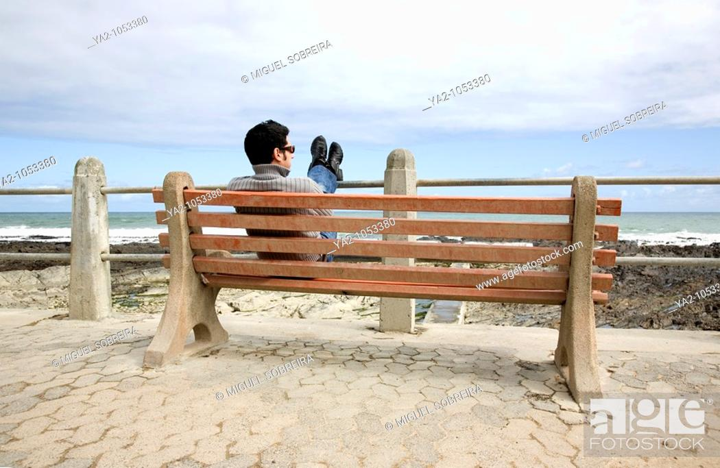 Photo de stock: Man sitting on bench at Sea Point beachfront in Cape Town.