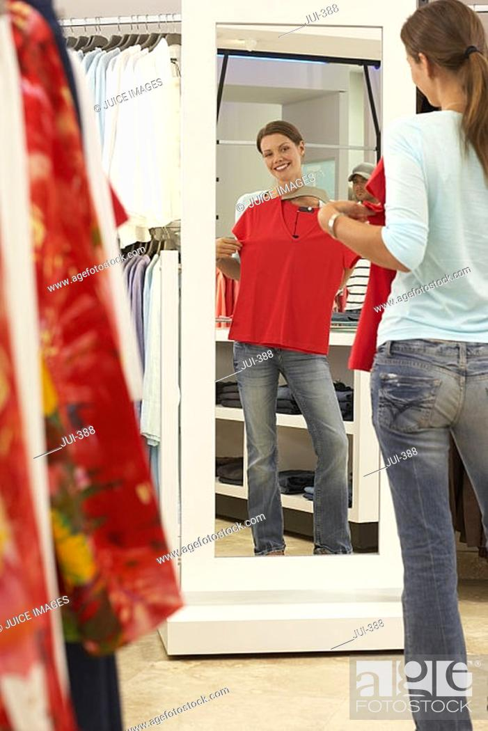 Stock Photo: Woman trying on red top in clothes shop, looking at reflection in mirror, smiling, rear view.
