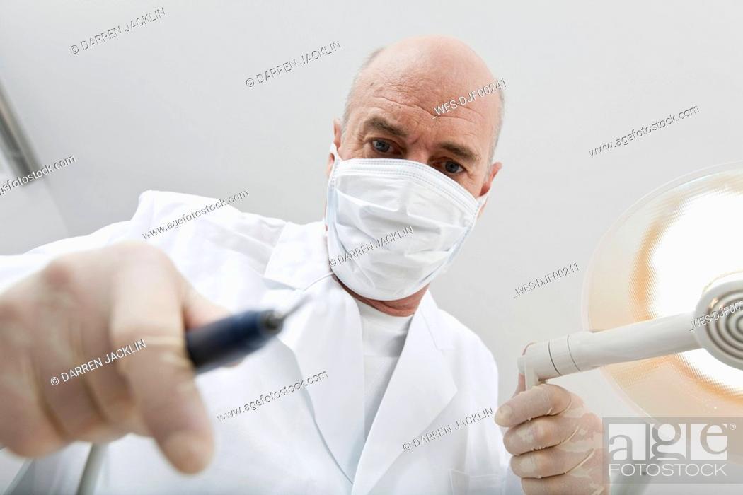 Stock Photo: Germany, Bavaria, Landsberg, Dentist wearing mask holding medical equipment,.