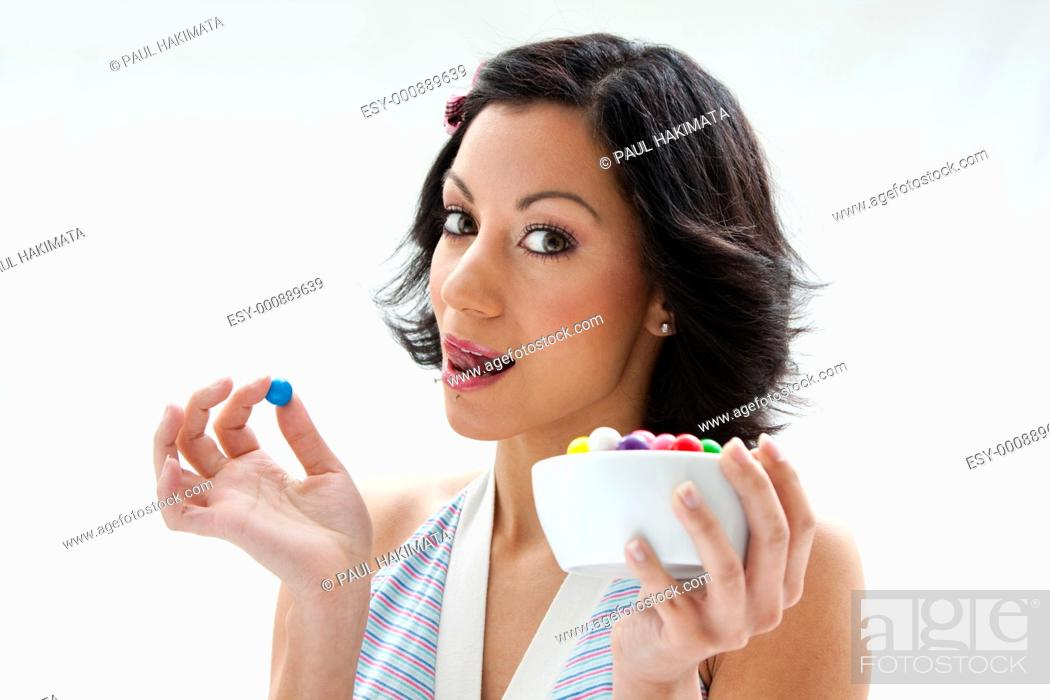 Stock Photo: Happy beautiful candy girl with a bowl of colorful bubblegum candy balls licking her lip, isolated.