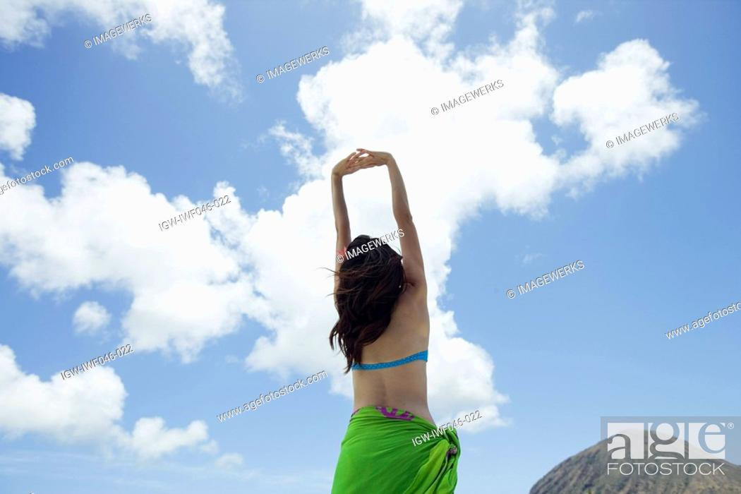 Stock Photo: Rear view of a woman with hands raised.