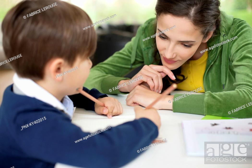Stock Photo: Woman teaching her son at home.