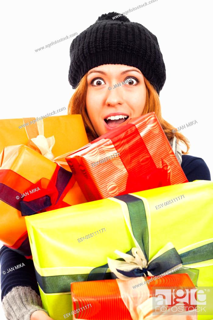 Stock Photo: Ecstatic happy woman in winter hat holding many colorful gift boxes, isolated on white background.