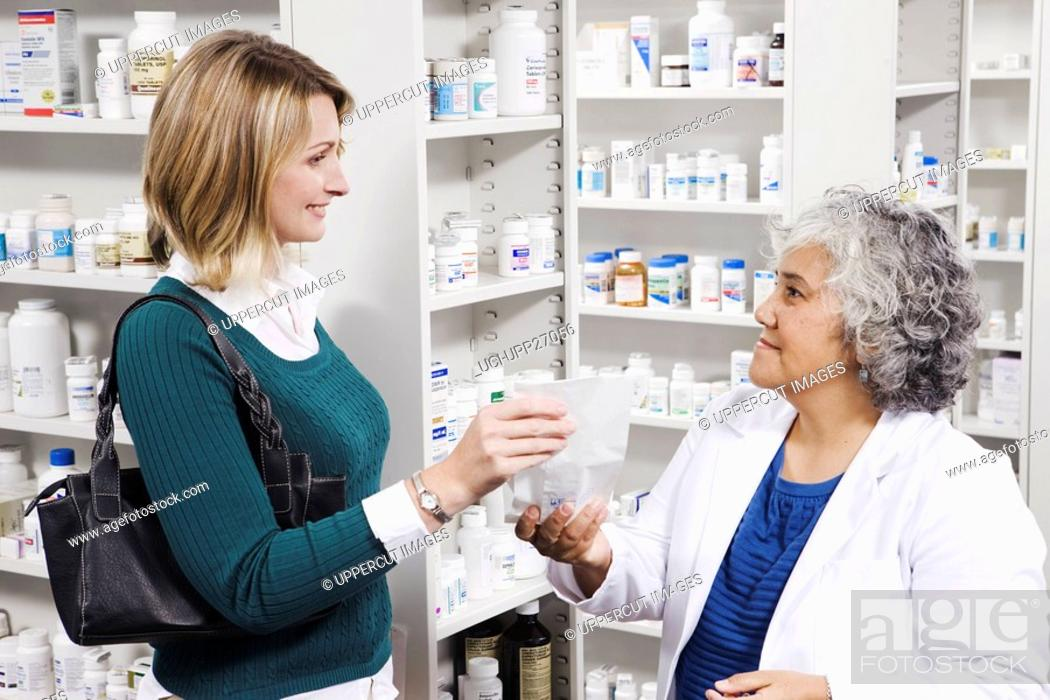 Stock Photo: Pharmacist giving prescription to customer.