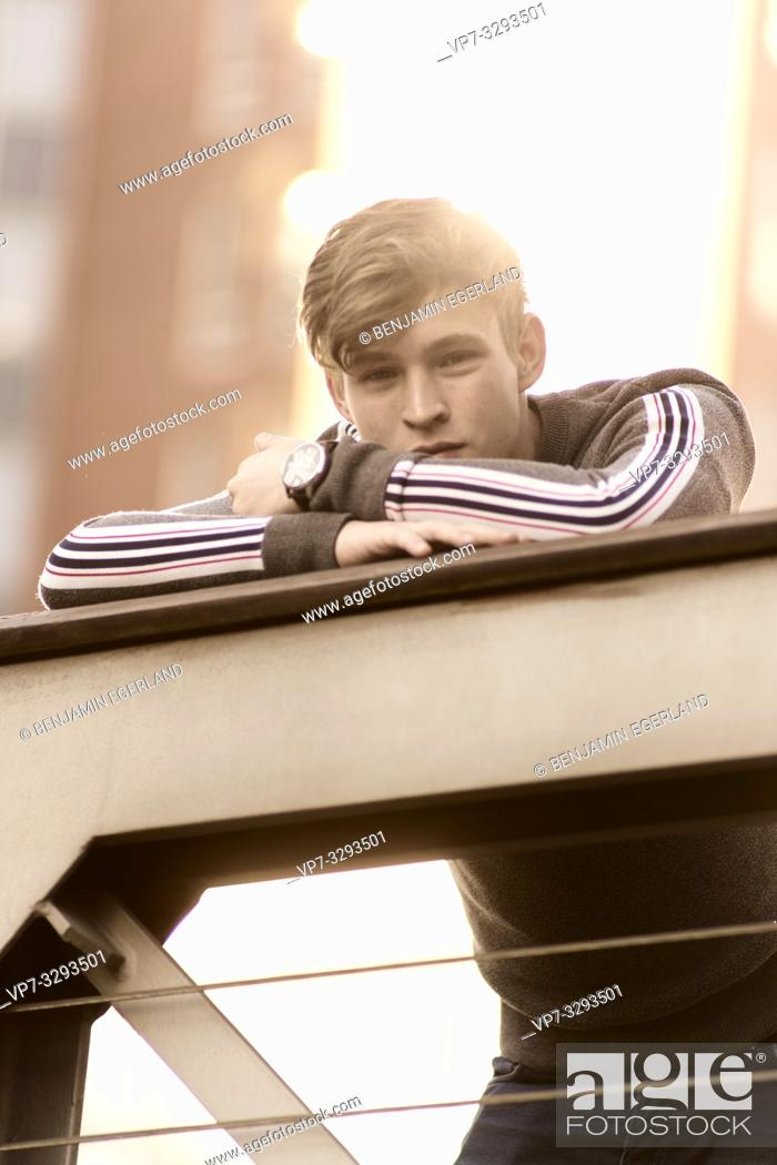 Stock Photo: young relaxed model man leaning on railing, in Hamburg, Germany.
