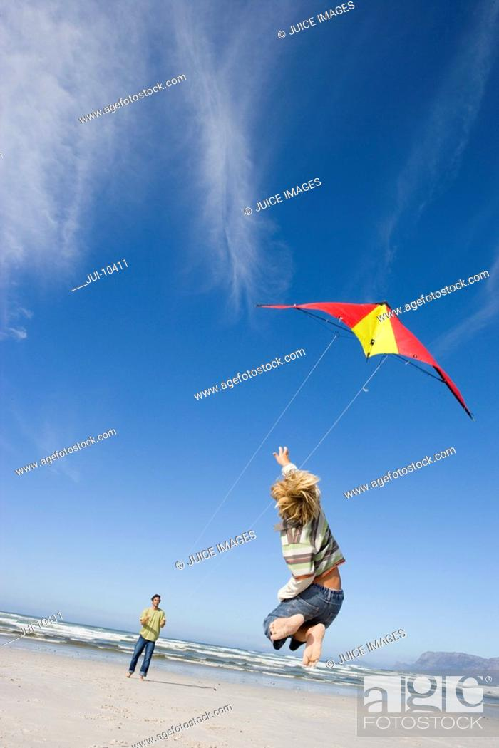Stock Photo: Boy 6-8 jumping by father flying kite on beach, rear view.